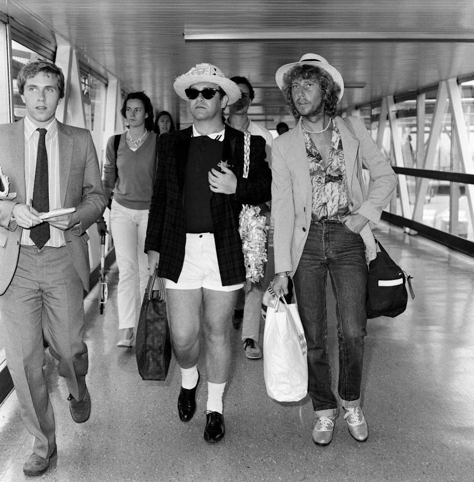 <p>If you ever wondered what Elton John wore on vacation, this is it. The singer was still clearly on island time as he traveled to London from Antigua wearing white shorts, a blazer, and a straw hat, naturally. </p>