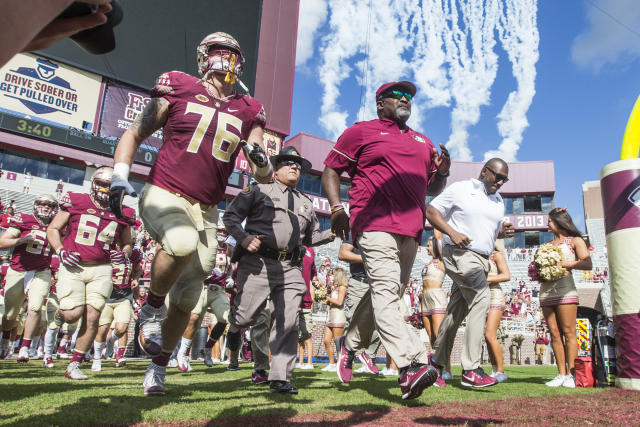 Florida State interim head coach Odell Haggins, center, and offensive lineman Rick Leonard take the field before an NCAA college football game against Louisiana Monroe in Tallahassee, Fla., Saturday, Dec. 2, 2017. (AP Photo/Mark Wallheiser)