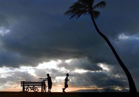 TWO BOYS PLAY AT SUNSET IN HONOLULU.
