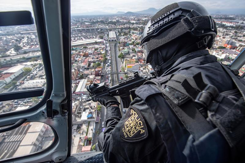 A policeman is seen on board of a helicopter of the Condor group as it overflies Mexico City, on August 2, 2018. - Mexican President-elect Andres Manuel Lopez Obrador, who will take office on December 1, 2018 inherits a messy war on drug cartels from his predecessor Enrique Pena Nieto. Since Mexico deployed its army to fight drug trafficking in 2006 during the presidency of Felipe Calderon, the country has been engulfed in a wave of violence that has left more than 200,000 murders, 30,000 missing, as well as complaints against the heavily armed security forces for violations, extrajudicial executions and forced disappearances. (Photo by Pedro PARDO / AFP) (Photo credit should read PEDRO PARDO/AFP/Getty Images)