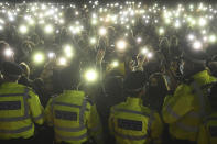 People gather and turn on their phone torches in Clapham Common, despite the Reclaim These Streets vigil for Sarah Everard being officially cancelled, in London, Saturday, March 13, 2021. A serving British police officer accused of the kidnap and murder of a woman in London has appeared in court for the first time. Wayne Couzens, 48, is charged with kidnapping and killing 33-year-old Sarah Everard, who went missing while walking home from a friend's apartment in south London on March 3. (Victoria Jones/PA via AP)