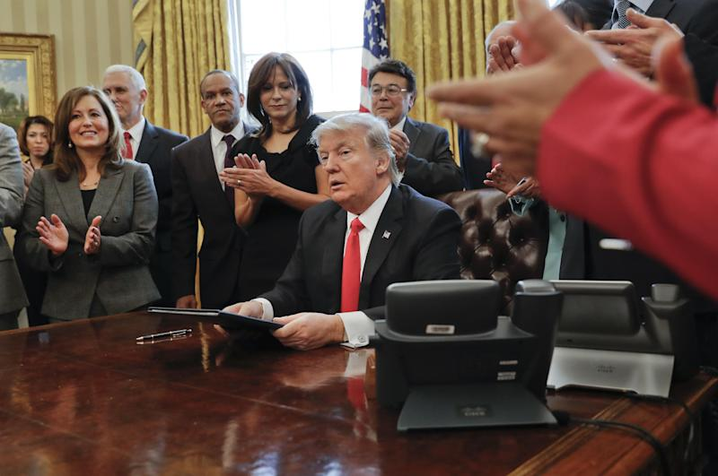 """Small business leaders applaud President Donald Trump after he signed an executive order in the Oval Office of the White House in Washington, Monday, Jan. 30, 2017. Trump order is aimed at significantly cutting regulations. White House officials are calling the directive a """"one in, two out"""" plan. It requires government agencies requesting a new regulations to identify two regulations they will cut from their own departments. (AP Photo/Pablo Martinez Monsivais)"""