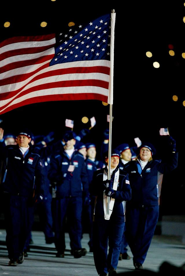 400804 82: (NEWSWEEK, U.S. NEWS, MACLEANS & GERMANY OUT) Amy Peterson of the U.S. carries the national flag as her teammates walk behind her during the Opening Ceremony of the 2002 Salt Lake City Winter Olympic Games at the Rice-Eccles Olympic Stadium February 8, 2002 in Salt Lake City, UT. (Photo by Al Bello/Getty Images)