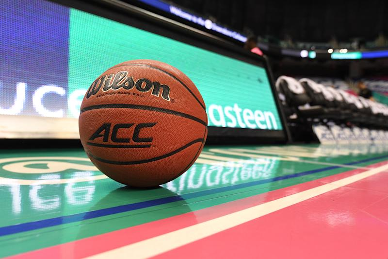 "A basketball that says ""ACC"" sits on the court."