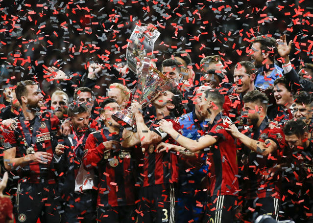 Atlanta United team captain Michael Parkhurst (3) kisses the trophy as teammates celebrate during the trophy presentation after the MLS Cup championship soccer game against the Portland Timbers, Saturday, Dec. 8, 2018, in Atlanta. Atlanta United won 2-0. (AP Photo/Todd Kirkland)