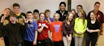 In this March 18, 2014 photo the 'Math Minions,' sixth graders at Oak Grove Middle School in Fargo, North Dakota, pose for a photo with Motif Investing founder Hardeep Walia, center right rear, and math teacher Dave Carlson, right rear, at Oak Grove Middle School in Fargo, North Dakota. Carlson started a competition between regular and advance math classes at Oak Grove and registered his students with Motif Investing, a company that enables customers to buy baskets of stocks. In the end, Carlson's regular math class yielded a nearly 22 percent gain and trounced every university club participating in a contest that was held at the same time. (AP Photo/Bruce Crummy)