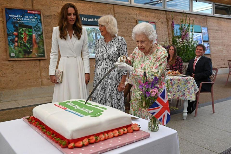 <p>At a reception for the G7 Summit in Cornwall, Queen Elizabeth cut a cake with a sword, lent to her by The Lord-Lieutenant of Cornwall, Edward Bolitho. The Duchess of Cambridge and Duchess of Cornwall looked on as the Queen sliced the dessert. </p>