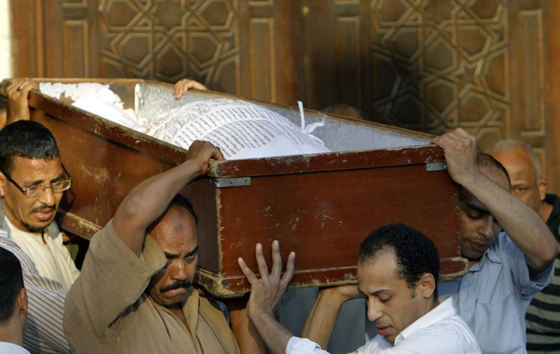 Egyptians carry the coffin of a Shiite following funeral prayers in Cairo, Egypt, Monday, June 24, 2013. Egypt's Islamist president condemns the killing of four Shiites by a Sunni Muslim mob that beat the men to death in their homes. But critics say he is in part to blame for implicitly supporting his hard-line allies as they stir up incitement against Shiites over Syria's civil war, and they warn that militant Islamists are acting with impunity. (AP Photo/Amr Nabil)