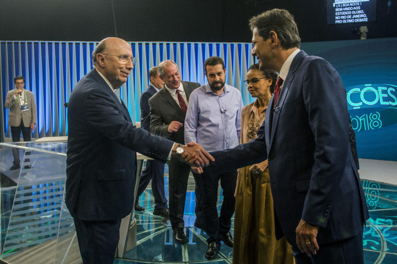 Brazilian presidential candidates Henrique Meirelles (MDB) (L) and Fernando Haddad (PT) (R) shake hands, backdroped by Alvaro Dias (Podemos), Ciro Gomes (PDT) , Guilherme Boulos (PSOL) and Marina Silva (Rede) before the start of the last televised presidential debate ahead of the October 7 general election, at Globo television network headquarters in Rio de Janeiro, Brazil on October 04, 2018. - Right-wing frontrunner Jair Bolsonaro, who was stabbed on September 6 during a campaign rally in the southern state of Minas Gerais, is absent due to medical reasons. (Photo by Daniel RAMALHO / AFP) (Photo credit should read DANIEL RAMALHO/AFP via Getty Images)