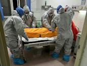 Medical workers prepare to take away the body of Covid-19 victim Zhang Lifa, the father of Zhang Ha, in a hospital in Wuhan, China on February 1