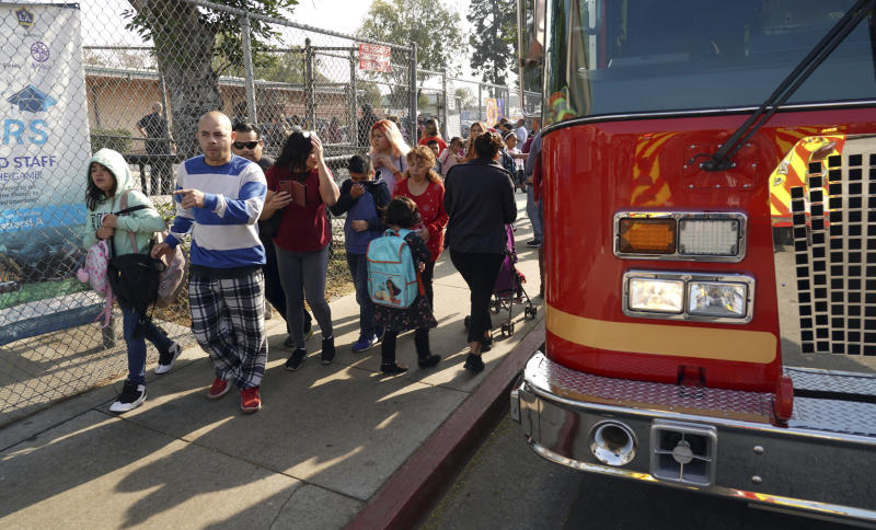 Parents and children leave Park Avenue Elementary School after jet fuel fell on the school in Cudahy, Calif., Tuesday, Jan. 14, 2020. Jet fuel dumped by an aircraft returning to Los Angeles International Airport fell onto the school playground where children were playing Tuesday, fire officials said. The Los Angeles County Fire Department said firefighters assessed over a dozen children and several adults who complained of minor injuries and none needed to be taken to a hospital. (Scott Varley/The Orange County Register via AP)