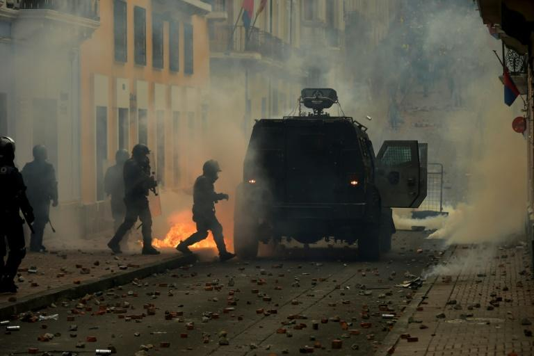 Riot police confront demonstrators during clashes in Quito