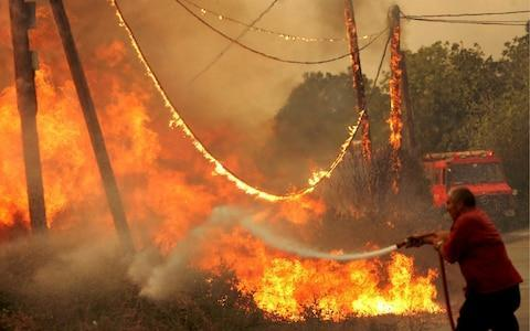 <span>A Greek firefighter battles the fire at the village of Styra on the island of Evia, Greece, in August 2007</span> <span>Credit: Margarita Kiaou/EPA </span>