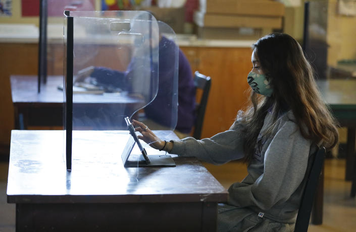LONG BEACH, CA - MARCH 24:                                                       Senior student Ariana Diaz with a plexiglass barrier in the art classroom of Art 2 teacher Patty Steponovich as students return to in-person instruction at St. Anthony Catholic High School in Long Beach March 24, 2021. The students have not returned to campus since March 2020 due to the Covid-19 pandemic. The hybrid model that will be used at St. Anthony's will allow 60% of the school's 445 students to return for full-time, in-person instruction and splitting those to rotating days so roughly 134 students per day on campus, while also continuing remote learning for those who opt to remain at home. On campus Covid-19 safety measures include temperature checks, face masks, social distancing and plexiglass barriers around desks. President of St. Anthony High School Gina Maguire says they are working to get all students back on campus by May.     St. Anthony Catholic High School on Wednesday, March 24, 2021 in Long Beach, CA. (Al Seib / Los Angeles Times via Getty Images).