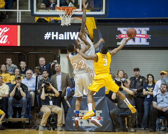 West Virginia's Juwan Staten, right, drives to the basket as Kansas' Andrew Wiggins (22) and Jamari Traylor defends during the first half of an NCAA college basketball game Saturday, March 8, 2014, in Morgantown, W.Va. (AP Photo/Andrew Ferguson)