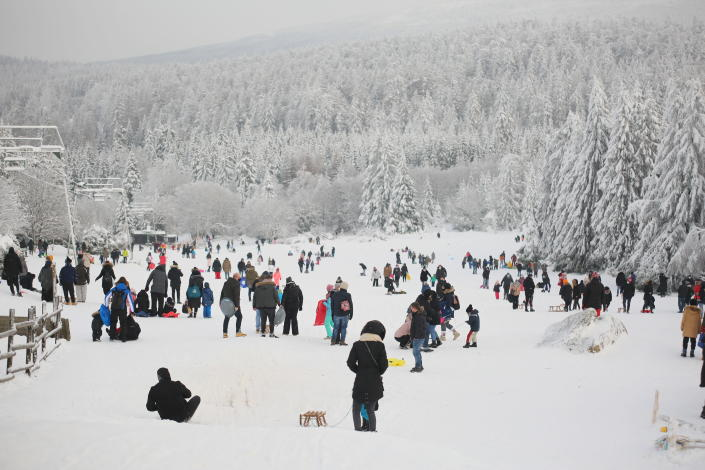 Well attended are the toboggan slopes at Torfhaus, Germany, Sunday, Jan. 17, 2021. Many visitors came to the Harz to enjoy the winter weather, even when the corona rules demand social distancing. (Matthias Bein/dpa via AP)
