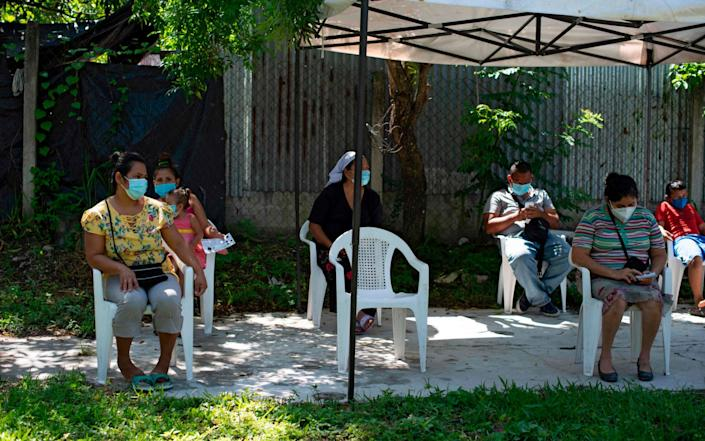 Residents maintain social distance while waiting to see a doctor in a clinic of the organization Doctors Without Borders in Soyapango, El Salvador - AFP
