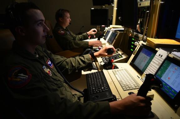 Two drone operators remotely fly an MQ-1 Predator aircraft on Oct. 22, 2013.