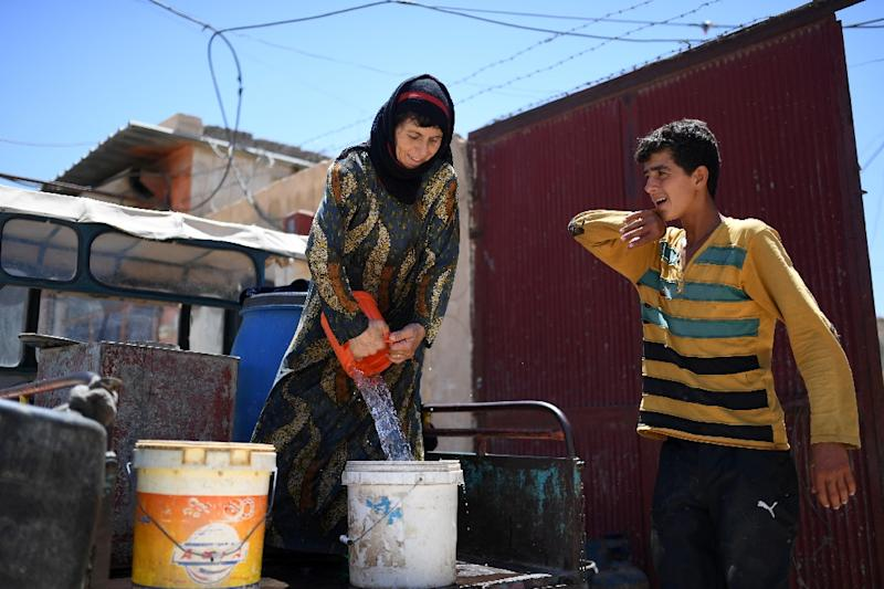 Al-Jassem fills a bucket with water for her grape vine on a visit to her home on July 15, 2017, five weeks after leaving during fighting between US-backed forces and Islamic State militants (AFP Photo/BULENT KILIC)