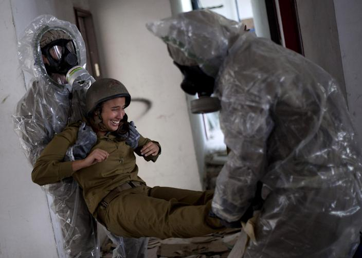 Israeli soldiers of the Home Front Command rescue unit wear protective gear during a drill in Azur, near Tel Aviv, Israel, Tuesday, May 28, 2013. Israel has launched a national civil defense drill, which the army said this year will focus on the threat of unconventional weapons at a time of growing regional tensions. (AP Photo/Ariel Schalit)