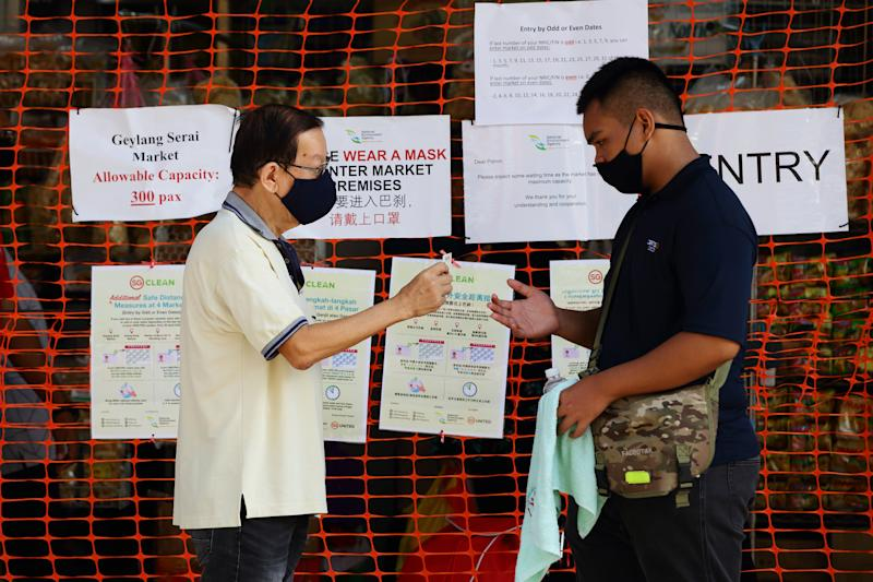 SINGAPORE - APRIL 23: A man wearing protective mask shows his identification card before entering a wet market on April 23, 2020 in Singapore. The Singapore government further enhanced stringent measures by closing more workplaces and imposing entry restriction to popular places and will extend the partial lockdown until June 1 to bring down the coronavirus (COVID-19) cases within the community. (Photo by Suhaimi Abdullah/Getty Images)