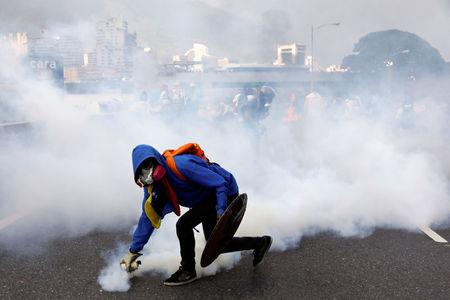 A demonstrator throws back a tear gas grenade at the riot police while rallying against Venezuela's President Nicolas Maduro in Caracas