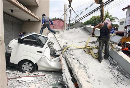 Workers use a crane to lift up concrete block that fell on a car after buildings collapsed during an earthquake in Cebu city, central Philippines October 15, 2013. REUTERS/Stringer