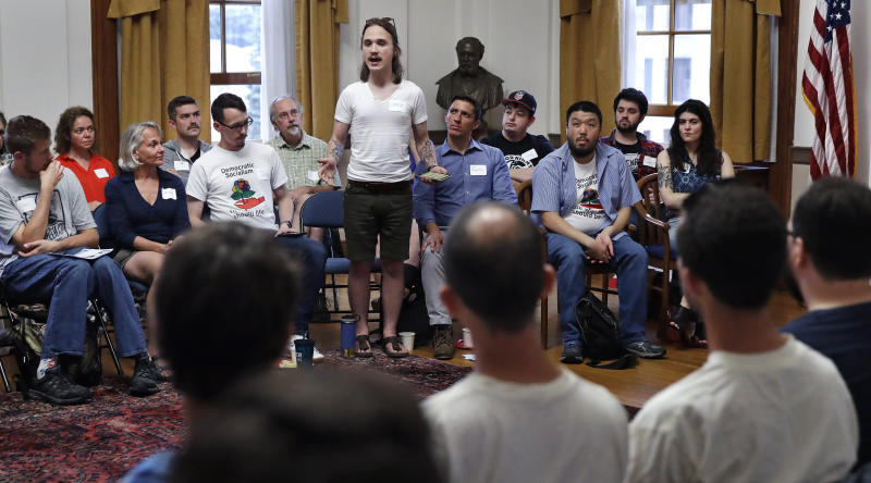 Corey Butler, center, stands as he explains what democratic socialism is to him during a meeting of the Southern Maine Democratic Socialists of America at City Hall in Portland, Maine, Monday, July 16, 2018. On the ground in dozens of states, there is new evidence that democratic socialism is taking hold as a significant force in Democratic politics. (AP Photo/Charles Krupa)