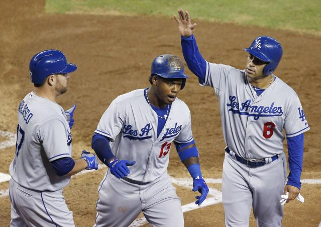 Los Angeles Dodgers' Hanley Ramirez, center, celebrates his three-run home run against the Arizona Diamondbacks with teammates Jerry Hairston Jr. (6) and Ricky Nolasco in the third inning of a baseball game on Thursday, Sept. 19, 2013, in Phoenix. (AP Photo/Ross D. Franklin)