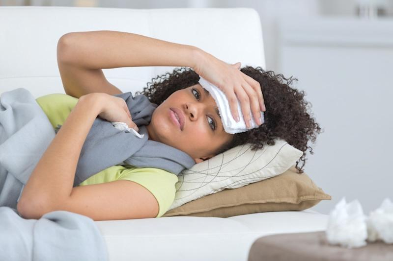 young woman sitting on a couch having a strong headache