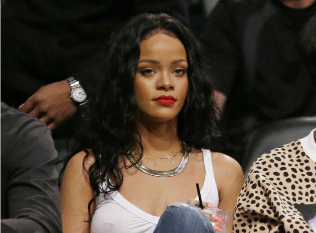 """FILE - This April 25, 2014 file photo shows singer Rihanna watching Game 3 of an NBA basketball first-round playoff series between the Brooklyn Nets and the Toronto Raptors in New York. CBS said Tuesday, Sept. 16, 2014 it was permanently editing a song featuring Rihanna's voice out of its Thursday night NFL telecasts _ after the singer issued a profane tweet about it. A portion of Jay-Z's """"Run This Town"""" featuring Rihanna was cut out of last Thursday's game because the network was covering the controversy over Rice's assault of his then-fiancee. CBS had planned to use the song Thursday and for the rest of the season, but Rihanna tweeted her objections. CBS issued a statement saying that it was """"moving in a different direction"""" with different theme music. (AP Photo/Frank Franklin II, File)"""