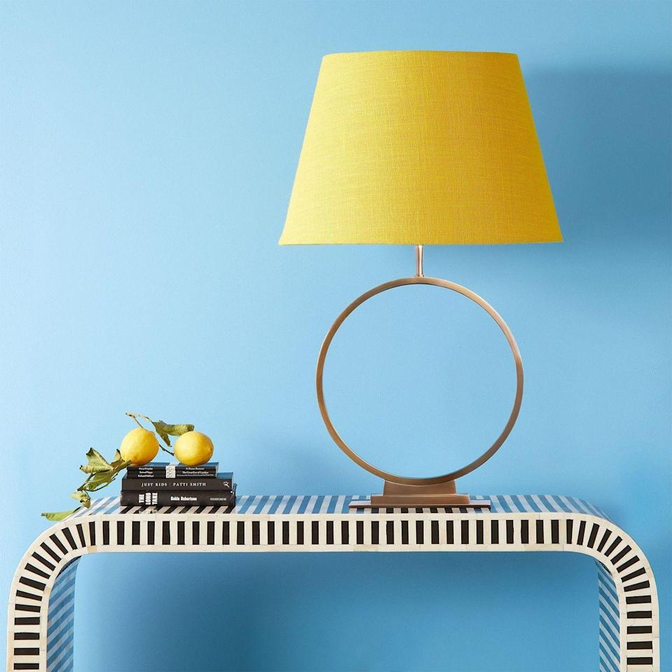 """<p>One for the colour lovers, this striking empire lampshade in a bright lemon yellow is a feature in itself. It will match perfectly with blue, as shown here, but yellow is deceptively versatile, making an equally happy match with forest greens, or warm reds. </p><p><strong>Shop now: <a href=""""https://www.pooky.com/lampshades/50cm-straight-empire-shade-in-acid-yellow-jute-with-pink-lining#selection.config_size=45&selection.shade_fabric_color=JUTYEP"""" rel=""""nofollow noopener"""" target=""""_blank"""" data-ylk=""""slk:Straight Empire Lampshade in Acid Yellow at Pooky"""" class=""""link rapid-noclick-resp"""">Straight Empire Lampshade in Acid Yellow at Pooky</a></strong></p>"""