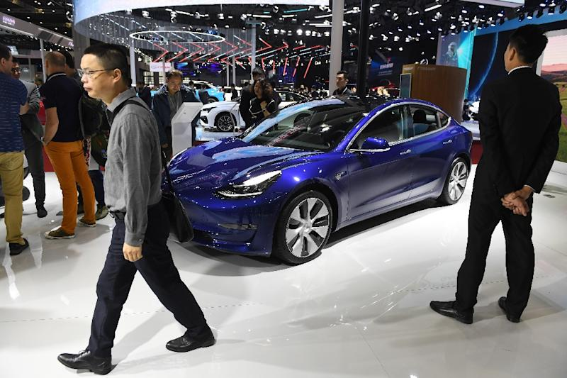 Visitors walk past a Tesla Model 3 at the Shanghai Auto Show in China on April 17, 2019 (AFP Photo/GREG BAKER)