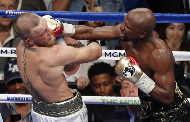 Floyd Mayweather Jr. hits Conor McGregor in a super welterweight boxing match in Las Vegas. (AP)