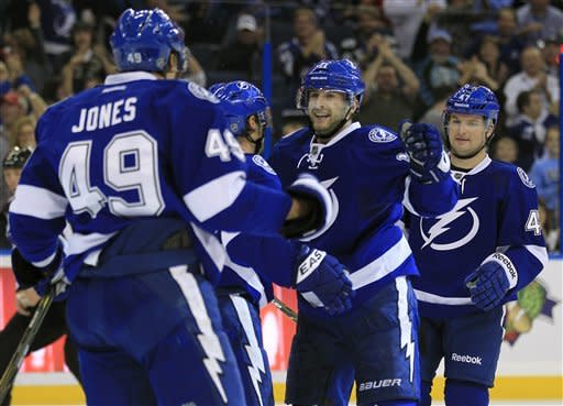 Tampa Bay Lightning left wing Tom Pyatt, second from right, celebrates with teammates, including Blair Jones, left, and Marc-Andre Bergeron, right, after scoring a goal against the Calgary Flames during the second period of an NHL hockey game on Thursday, Dec. 15, 2011, in Tampa, Fla. (AP Photo/Chris O'Meara)