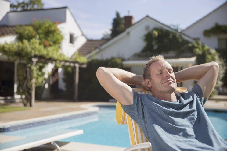 man relaxing on patio chair