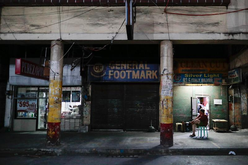 A man sits outside closed shops following the lockdown in the Philippine capital to prevent the spread of the coronavirus disease (COVID-19), in Manila, Philippines, March 24, 2020. REUTERS/Eloisa Lopez