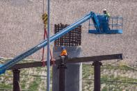 Work crews continue to work on the construction of a freeway overpass in San Diego