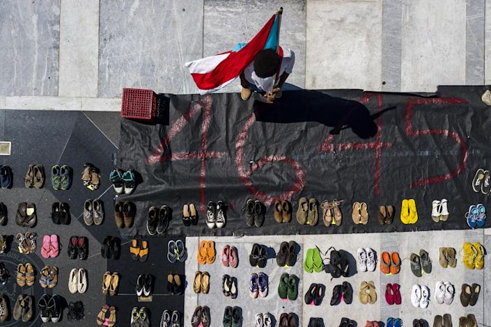 In this aerial photo, a demonstrator holds a Puerto Rican flag near empty pairs of shoes at the Puerto Rican Capitol during the protest June 1. (Photo: Xavier Garcia/Bloomberg)
