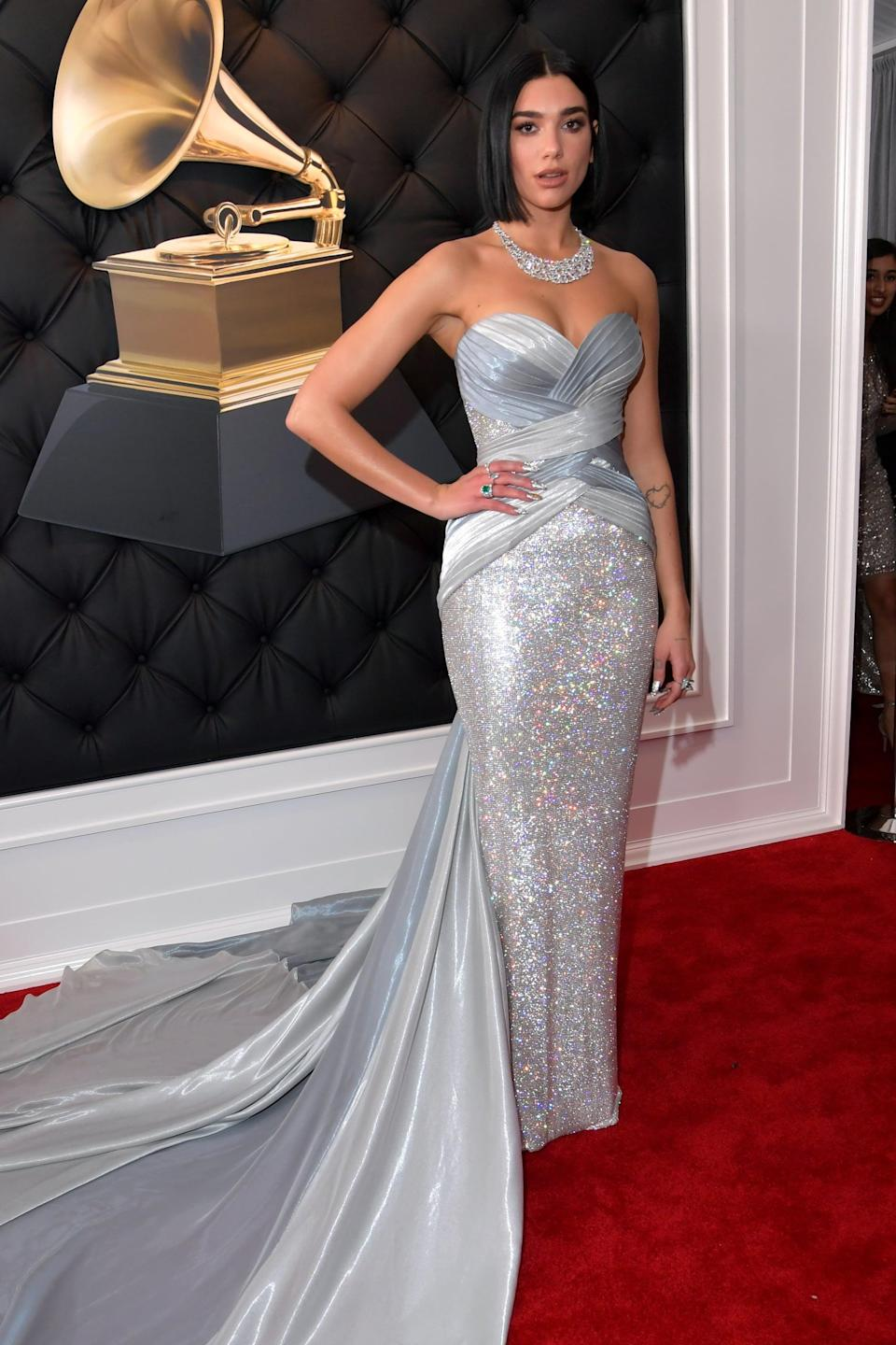 """<p><a rel=""""nofollow noopener"""" href=""""https://www.popsugar.com/fashion/Dua-Lipa-Dress-Grammy-Awards-2019-45773017"""" target=""""_blank"""" data-ylk=""""slk:Wearing a floor-sweeping silver strapless gown"""" class=""""link rapid-noclick-resp"""">Wearing a floor-sweeping silver strapless gown</a> with jewels from Bulgari and Ashley Zhang.</p>"""