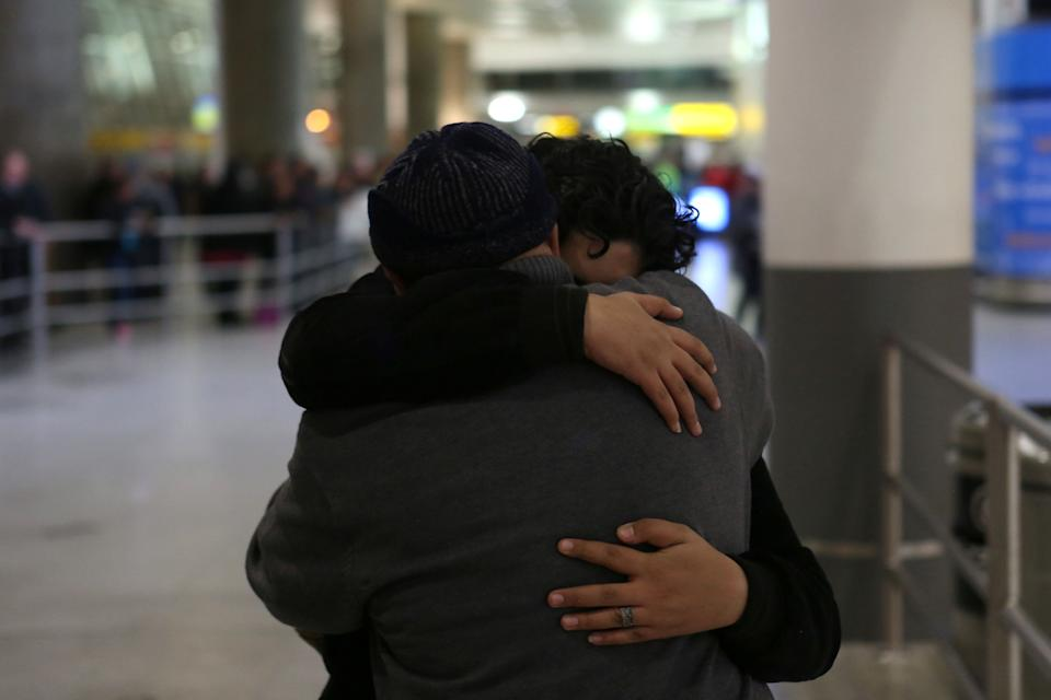 Ali Alghazali, 13, a Yemeni who was previously prevented from boarding a plane to the U.S., hugs his uncle Saleh Alghazali, upon Ali's arrival at Terminal 4 at JFK airport in Queens on Feb. 5, 2017, following the reprieve from the ban.