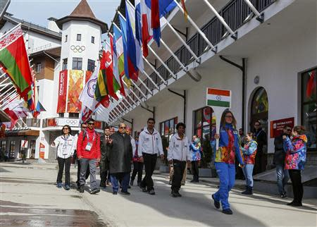 Members of India's national athletes team walk to attend the welcoming ceremony for the team in the Olympic athlete's village, which stands on a mountain plateau in Rosa Khutor, during the 2014 Winter Olympic Games