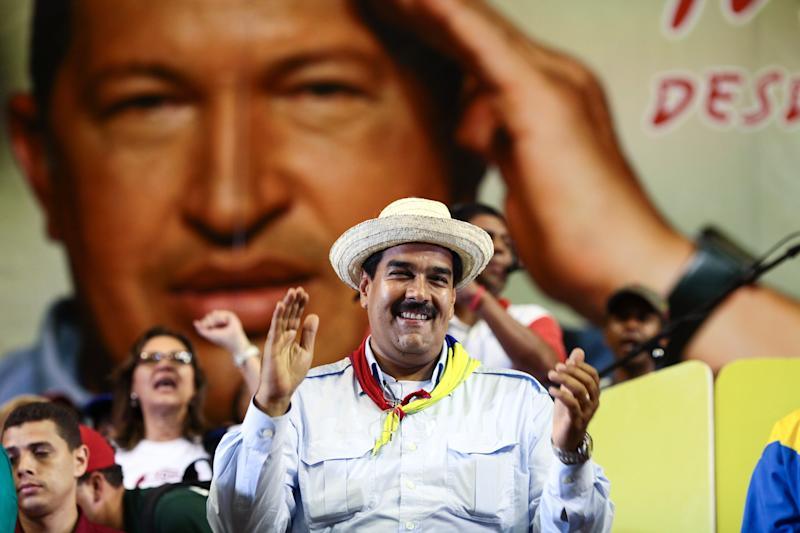 In this photo released by Miraflores Press Office, and taken Wednesday March 27, 2013, back dropped by a picture of the late Hugo Chavez Venezuela's acting President Nicolas Maduro greets supporters during a rally in Margarita Island, Venezuela. Holy Week in Venezuela is a time when millions traditionally take a welcome pause from work and politics to go on vacation. Yet that hasn't stopped Venezuela's time-pressed presidential candidates from sprinting through the holidays toward an April 14 election to replace the late Hugo Chavez, as they try to define both themselves and each other within weeks. Maduro Chavez's chosen successor, acting President Nicolas Maduro will run against opposition leader Henrique Capriles. (AP Photo /Miraflores Press Office)