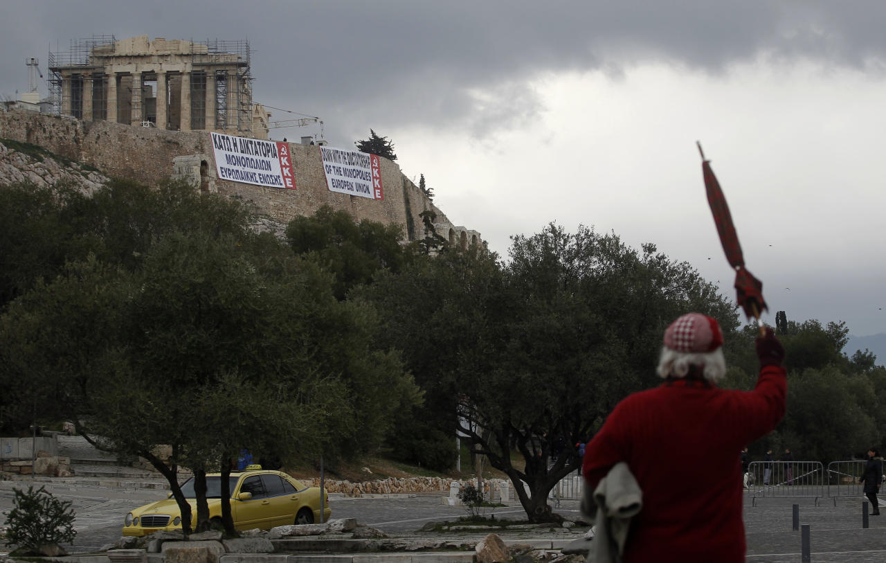 A Pedestrian gestures as banners in Greek and English denouncing EU policies are hung by Greek communist party members under the temple of Parthenon at the Athens' Acropolis hill on Saturday Feb. 11, 2012. Lawmakers from two parties backing Greece's coalition government are meeting Saturday to consider support for legislation containing new austerity measures, which Socialist leader George Papandreou has urged his deputies to back, saying the country faces disaster if the new bailout deal falls through. (AP Photo/Petros Giannakouris)
