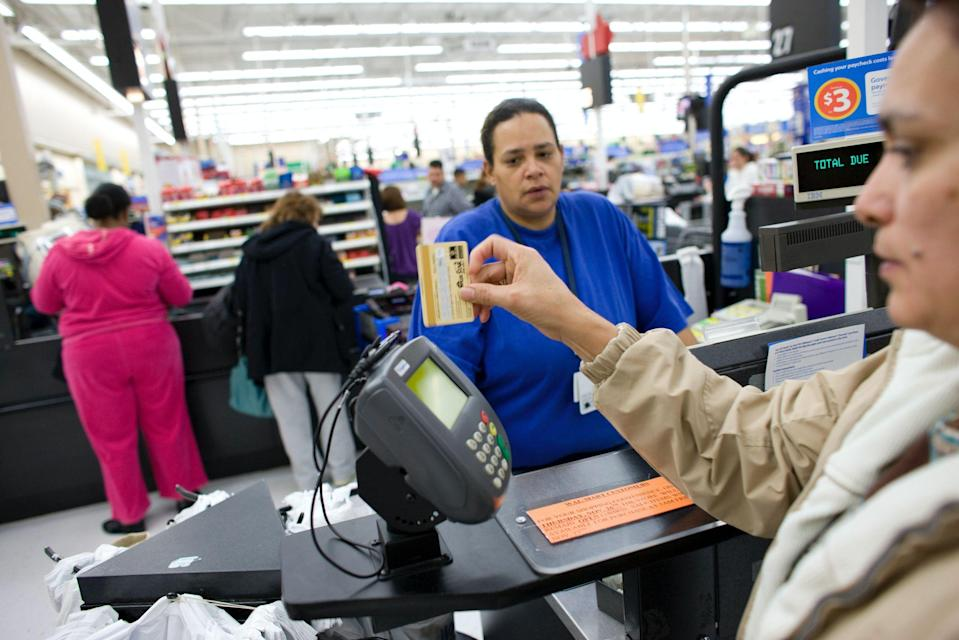A customer uses a card to pay for her items at a Wal-Mart Supercenter in Denver, Colorado, U.S., on Friday, Nov. 27, 2009. (Photo: Matthew Staver/Bloomberg via Getty Images)
