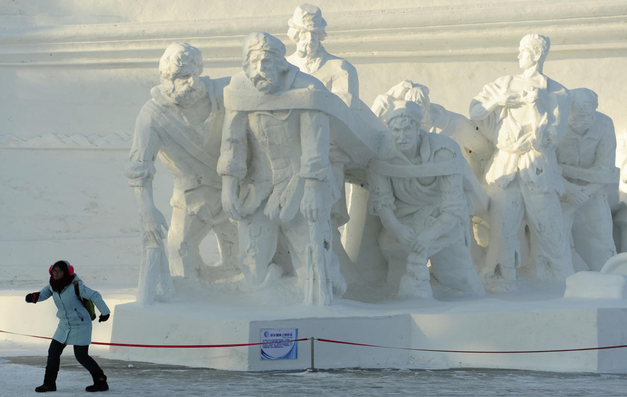 "A tourist poses for a photograph in front of a snow sculpture depicting the famous painting ""Barge Haulers on the Volga"" ahead of the 13th Harbin Ice and Snow World in Harbin, Heilongjiang province December 26, 2011. The Harbin International Ice and Snow Festival will be officially launched on January 5, 2012. REUTERS/Sheng Li (CHINA - Tags: ENVIRONMENT SOCIETY)"