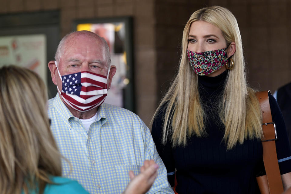 Ivanka Trump, right, and Secretary of Agriculture Sonny Perdue, left, speak with a farming family during a visit to the North Carolina State Farmers Market in Raleigh, N.C., Thursday, Sept. 10, 2020. (AP Photo/Gerry Broome)