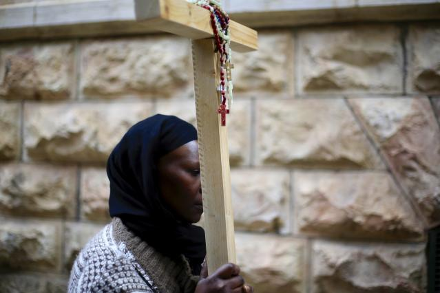 A Christian worshiper carries a cross walk along the Via Dolorosa towards the Church of the Holy Sepulchre, traditionally believed by many to be the site of the crucifixion of Jesus Christ, during the Good Friday procession in Jerusalem's old city, Friday, April 19, 2019. (AP Photo/Ariel Schalit)