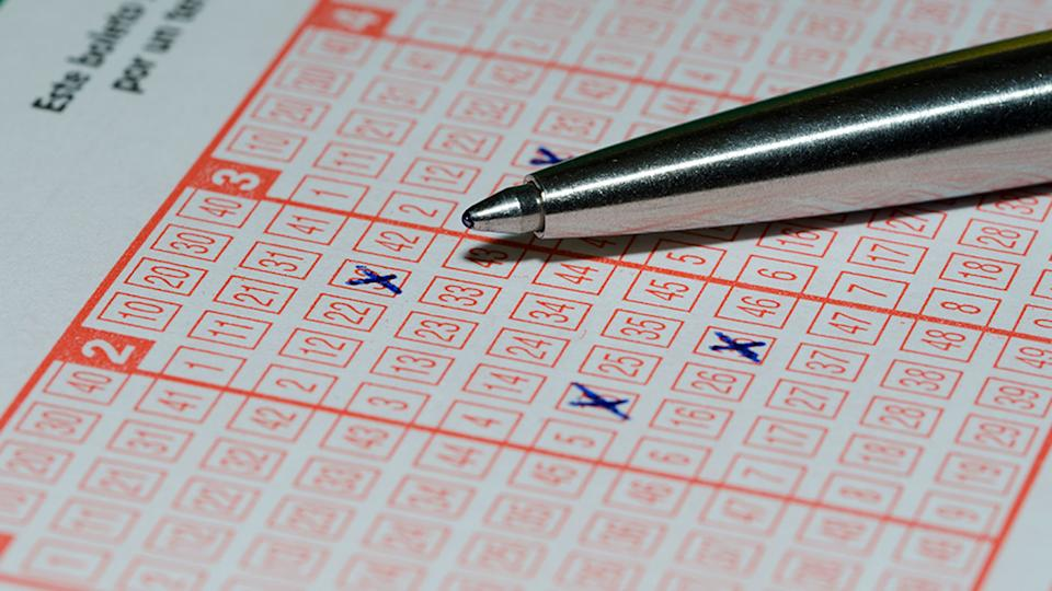 Pictured is a lottery ticket with numbers marked and a pen.
