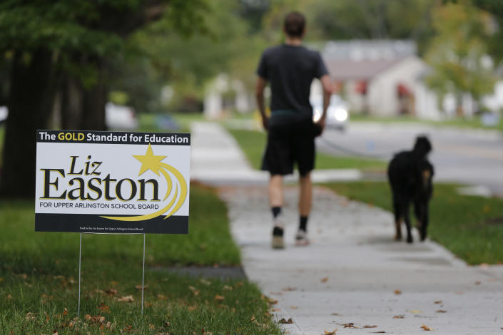A person walks their dog past a school board yard sign Thursday, Oct. 7, 2021, in Upper Arlington, Ohio. Across Ohio and the nation, parental protests over social issues like mask mandates, gender-neutral bathrooms, teachings on racial history, sexuality and mental and emotional health are being leveraged into school board takeover campaigns. (AP Photo/Jay LaPrete)